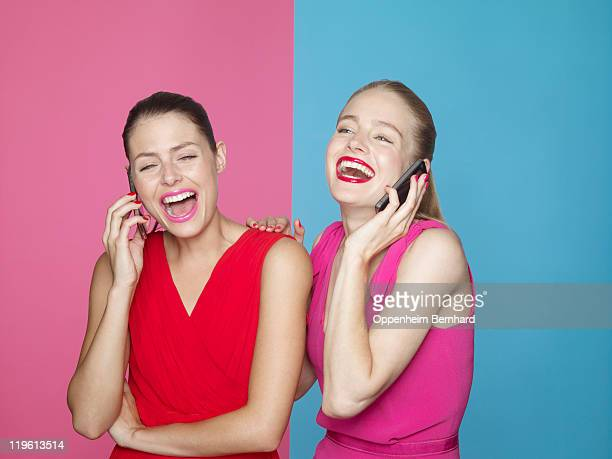 two laughing women on mobile phones - pink dress stock pictures, royalty-free photos & images