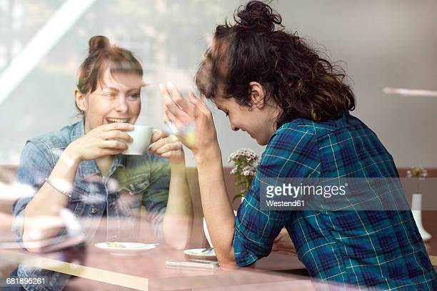 Two laughing women sitting behind windowpane of a coffee shop