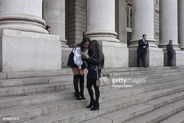 Two laughing young women pause to admire their photos on the steps of Royal Exchange on 9th December 2016 in the City of London England