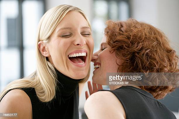 Two laughing young women whispering