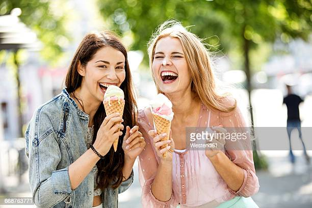 two laughing young women with ice cream cones - eis stock-fotos und bilder