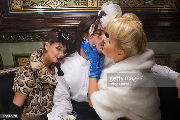 two lavishly dressed women flirting with a man - women dominating men stock photos and pictures