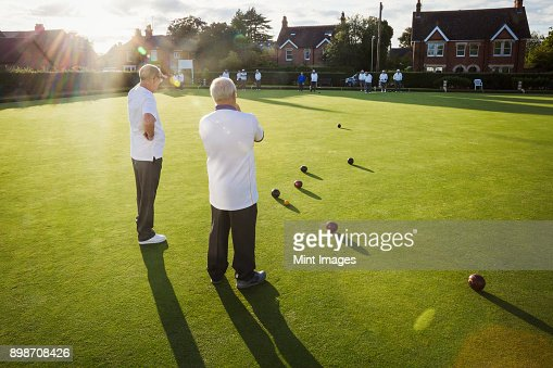 Two lawn bowls players, men standing discussing the game, and a clutch of lawn bowls on the playing surface.