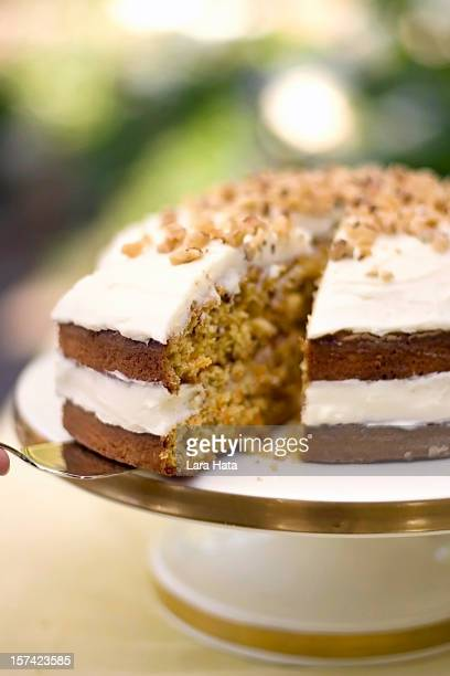 Two layer carrot cake being sliced and served