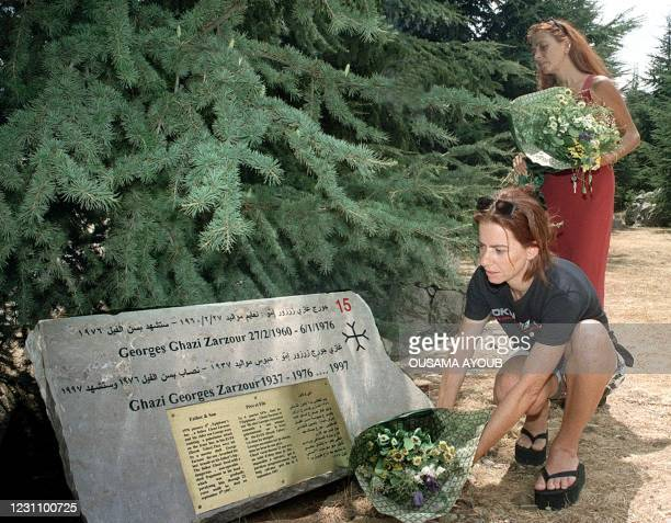 Two Lebanese women put flowers 31 August 1999 on their relative's tombstone at the Cedar of the Martyr war memorial, hidden away in the mountains in...