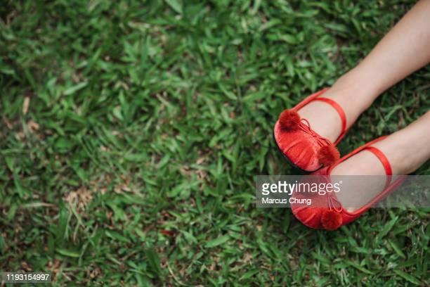 草の上に見えるかなり赤い靴を持つ2本の足 - 赤の靴 ストックフォトと画像