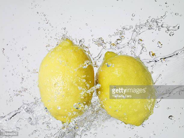 two lemons being splashed with water, close-up - レモン ストックフォトと画像