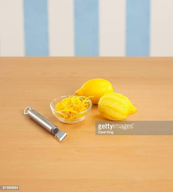 two lemons, bowl of rind and zester - dunschiller stockfoto's en -beelden