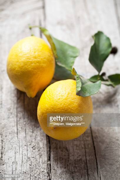 two lemons with leaves on a wooden surface - lemon leaf stock photos and pictures