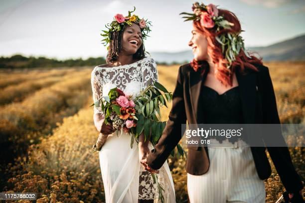 twee lesbische bruiden wandelen in de bloem veld - lesbische stockfoto's en -beelden