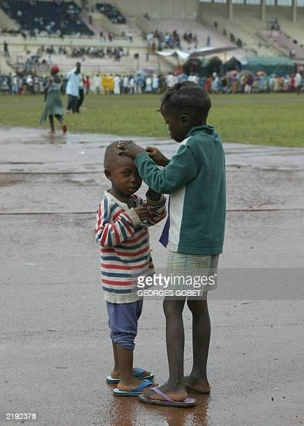 Two Liberian boys are seen at the Samuel Kanyon Doe stadium in Monrovia as other displaced people queue for food and goods distributed by the...