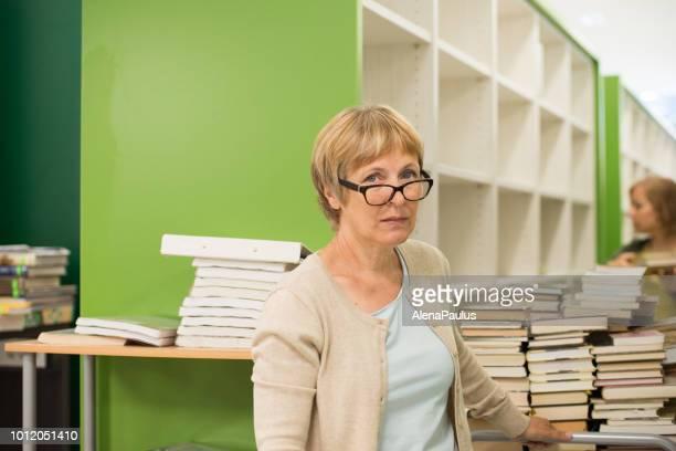 zwei frauen der bibliothekar bearbeiten, sortieren und erneuern die neue bibliothek - bücher im warenkorb - bibliothekar stock-fotos und bilder