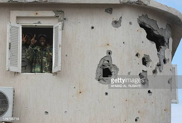 Two Libyan National Transitional Council fighters flash the Vsign for victory while standing on October 19 2011 behind a window of an empty house...