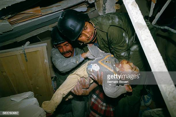 Two Libyans recover the dead body of a young boy from the debris of a building after American planes on a punitive mission bombed Tripoli