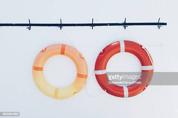 Two lifesavers hanging on a wall