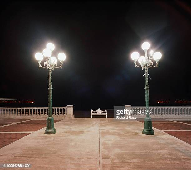 Two light posts with bench in distance