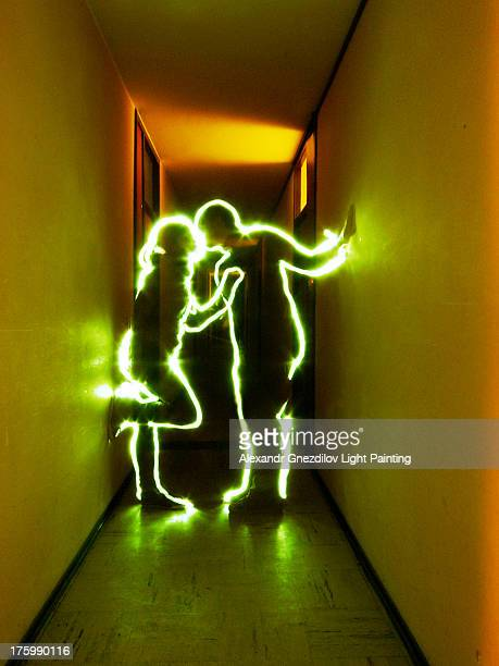 Two light silhouettes kissing in a dark corridor