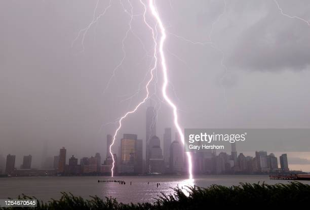 Two lightning bolts frame One World Trade Center as they hit the Hudson River in front of the skyline of lower Manhattan in New York City during a...