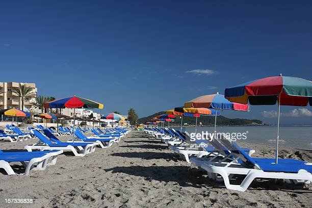 two lines of beach beds and sun umbrellas at Ibiza