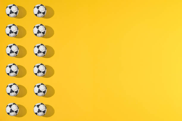 Two lines of old soccer balls on a yellow background to the left.