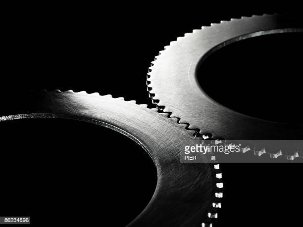 Two linked steel gear / cogs on black background