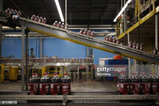 Two liter bottles of Dr Pepper brand soda move along a conveyor belt after being filled at the Dr Pepper Snapple Group Inc bottling plant in Irving...