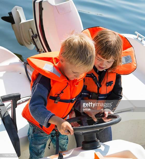 Two little blond friends in orange life jackets steering boat