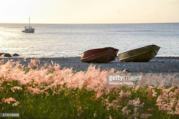 Two little boats in the shore of Kalki beach, during the sunset, in Curacao, Netherland Antilles A third fisherman boat can be seen at the...