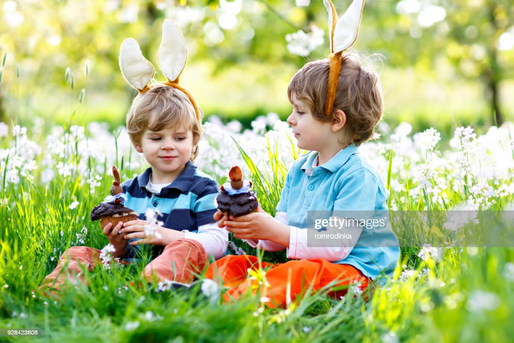 Two little boy friends in Easter bunny ears eating chocolate cakes and muffins : Stock Photo