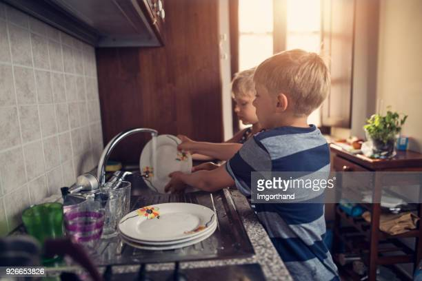 Two little boys cleaning dishes