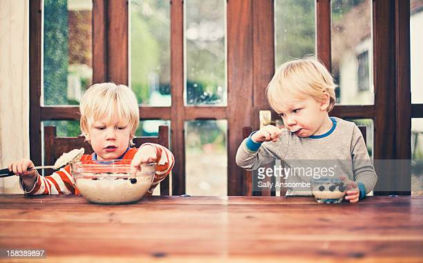 Two little boys eating porridge for breakfast