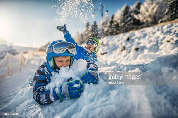 Deux petits garçons dans des tenues de ski jouant dans la neige fraîche