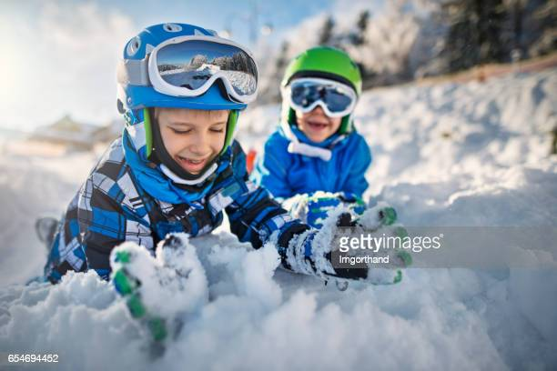 Two little boys in ski outfits playing in snow