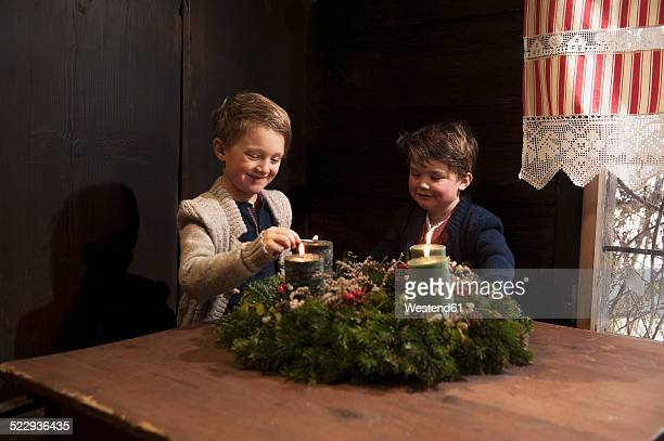 Two little boys lightning candles on a Advent wreath