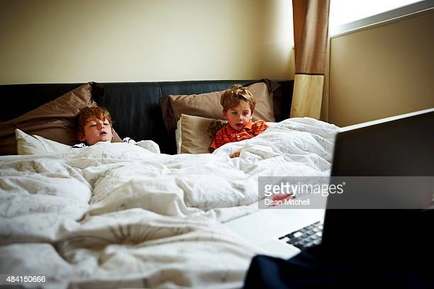 Two little boys lying in bed watching movie on laptop