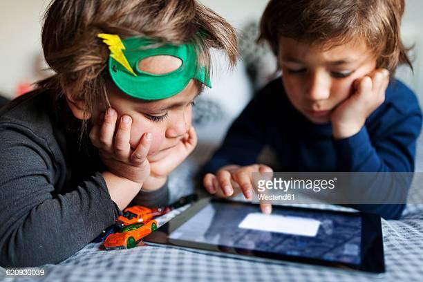 two little boys lying on bed playing with digital tablet - manos a la cabeza fotografías e imágenes de stock
