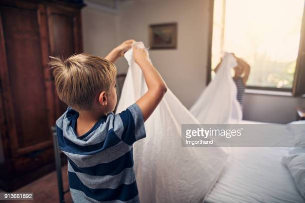 Two little boys making bed together
