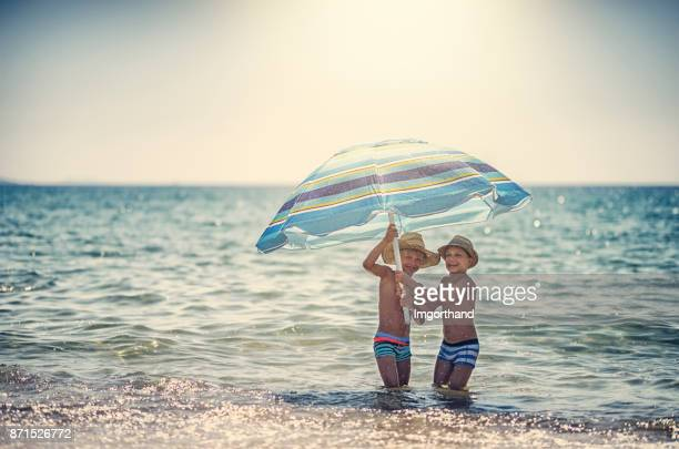 Two little boys playing in sea holding beach umbrella
