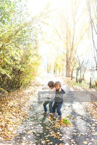 Two little boys playing on autumnal country road