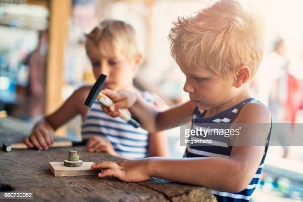 木材、ハンマーと釘で遊ぶ 2 つの男の子