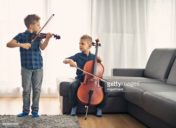 Two little boys practicing cello and violin together
