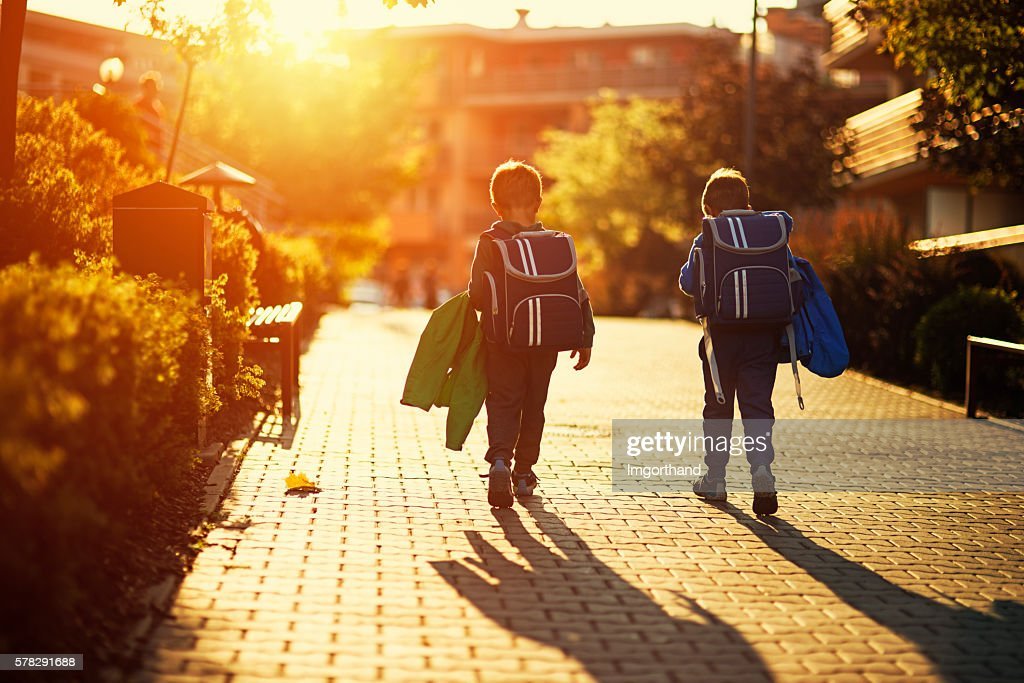 Two little boys returning from school : Stock Photo