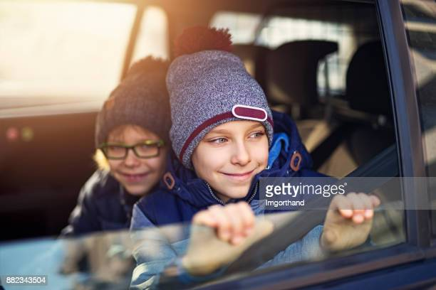 Two little boys riding to school in car