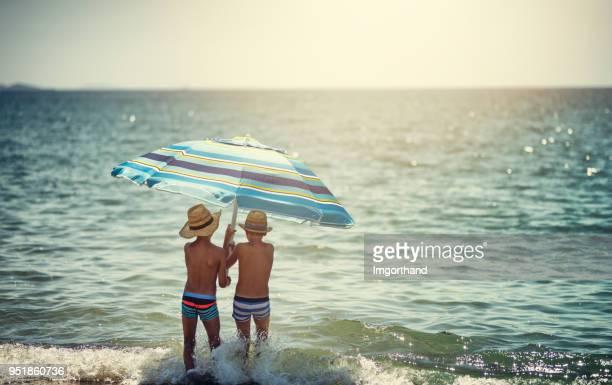 Two little boys scared of sunlight holding beach umbrella in sea