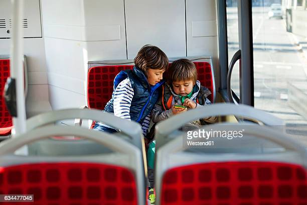 Two little boys sitting in a bus playing with smartphone
