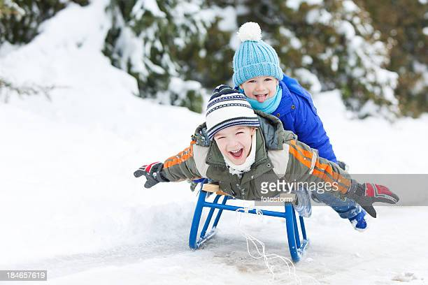 two little boys sledding on snow - tobogganing stock pictures, royalty-free photos & images