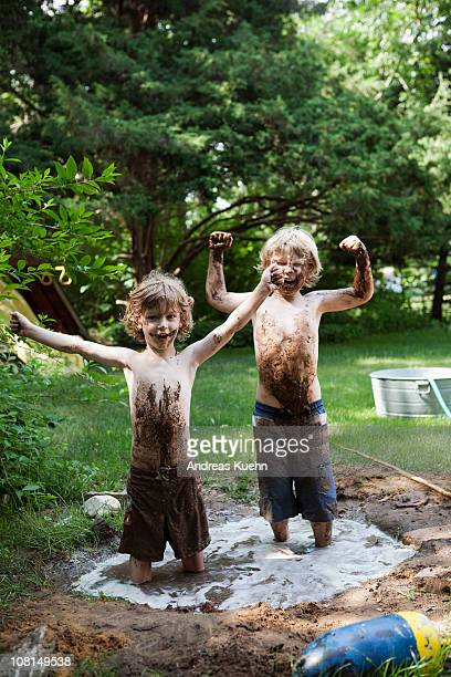 Two little boys standing in a mud hole.