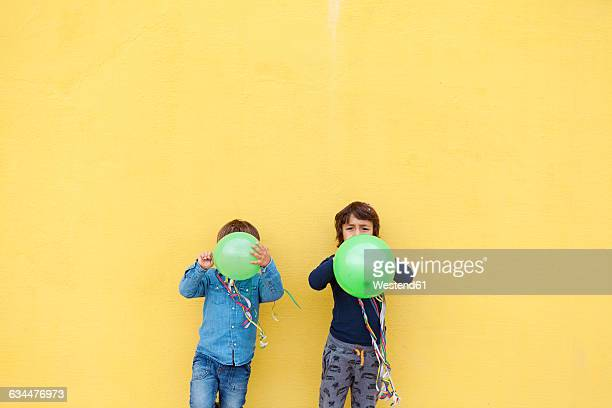 Two little boys with green balloons and streamers standing in front of yellow wall