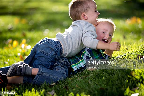 two little boys wrestling on the grass in a park - rough housing stock photos and pictures