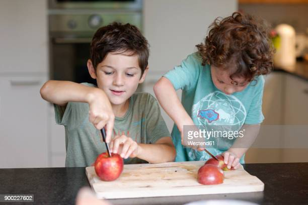 Two little brothers cutting apples in the kitchen